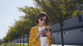 衣服和太阳镜的年轻女商人是保留片剂计算机在手和饮用的咖啡在都市街道上 影视素材