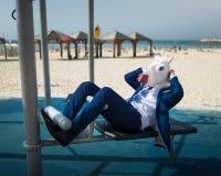 衣服和滑稽的面具的怪异的人做着体育在区域靠近海滩前 库存图片
