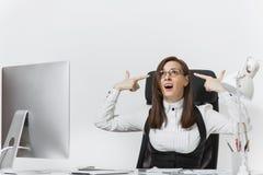 衣服和玻璃工作的美丽的女商人在有文件的计算机在轻的办公室 库存图片