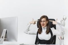 衣服和玻璃工作的美丽的女商人在有文件的计算机在轻的办公室 库存照片
