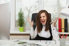 衣服和玻璃工作的美丽的女商人在有文件的计算机在轻的办公室 免版税库存照片