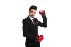 黑衣服和红色摆在演播室的拳击手套的年轻人 库存照片