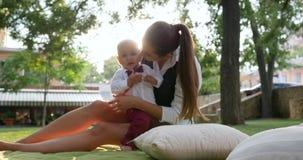 衣服和蝶形领结的美丽的男孩在妈妈附近休息坐绿色草坪 股票录像