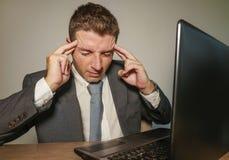 衣服和领带工作的年轻沮丧和被注重的商人被淹没在办公室手提电脑书桌遭受的头疼 免版税库存照片