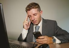 衣服和领带工作的年轻沮丧和被注重的商人被淹没在办公室手提电脑书桌遭受的头疼 免版税库存图片