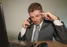 衣服和领带工作的年轻沮丧和被注重的商人被淹没在办公室手提电脑书桌遭受的头疼 库存图片