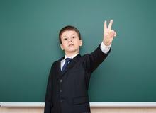 黑衣服展示两手指姿态的男生在绿色黑板背景,教育概念 免版税库存照片