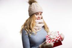 衣服暖和的美丽的年轻白肤金发的妇女有礼物盒的在手边在白色背景 戴米黄被编织的帽子的愉快的女孩, 库存图片