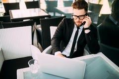 衣服松弛外部的英俊的商人与在某处大阳台的膝上型计算机在咖啡店谈话在电话 库存照片