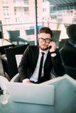 衣服松弛外部的英俊的商人与在某处大阳台的膝上型计算机在咖啡店谈话在电话 图库摄影