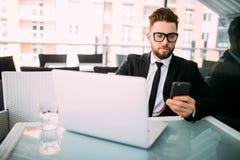 衣服松弛外部的英俊的商人与在某处大阳台的膝上型计算机在咖啡店键入在手机的 免版税库存图片
