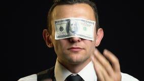 衣服的一个人黏附他的与一百元钞票的眼睛 影视素材
