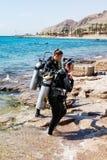 衣服的两名轻潜水员佩戴水肺的潜水的去水在埃拉特市附近在以色列 图库摄影
