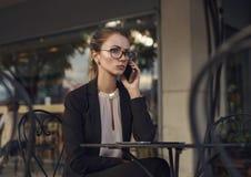 衣服的严肃的女商人谈话在手机 库存图片