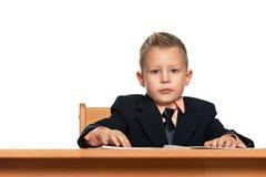 衣服的严肃的小男孩在书桌 图库摄影