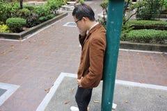 衣服的严肃的年轻商人谈话在手机,当倾斜杆在室外公园时 库存图片
