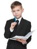 黑衣服的严肃的男小学生与笔记本 免版税库存照片