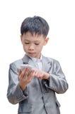衣服的亚裔男孩使用手机 免版税库存图片