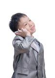 衣服的亚裔男孩谈话在白色背景的手机 免版税图库摄影
