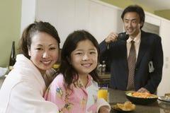 衣服的人与妇女和女孩前景的在厨房 图库摄影