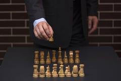 衣服的人做在下棋比赛的接下来的步骤 免版税库存图片