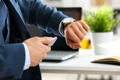 衣服的人和领带检查时间在银色手表 库存照片