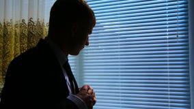 衣服的人在窗口附近 投入在他的夹克的新郎 我等待此的` ve