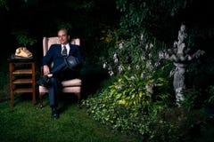 衣服的人坐椅子在繁茂花园里 免版税库存照片