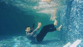 衣服的人游泳在水下,显示赞许并且享受女性腿 股票视频