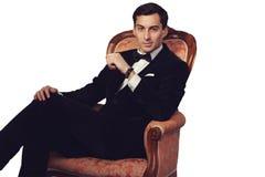 衣服的典雅的人坐葡萄酒扶手椅子 豪华 免版税库存图片