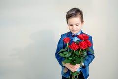 衣服的可爱的小男孩与英国兰开斯特家族族徽花束在轻的背景的 免版税库存照片