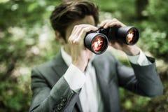 衣服的商人与看在他的市场上的双筒望远镜竞争者在绿色公园 到达天空的企业概念金黄回归键所有权 免版税图库摄影