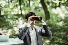 衣服的商人与看在他的市场上的双筒望远镜竞争者在绿色公园 到达天空的企业概念金黄回归键所有权 公执行委员是searc 免版税库存照片