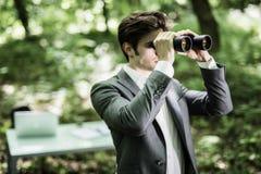 衣服的商人与看在他的市场上的双筒望远镜竞争者在绿色公园 到达天空的企业概念金黄回归键所有权 自由职业者执行委员是 库存照片