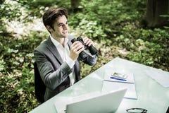 衣服的商人在他的有看在他的市场上的双筒望远镜的办公桌竞争者在绿色公园 绿色办公室 事务 免版税库存图片