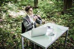 衣服的商人在他的有看在他的市场上的双筒望远镜的办公桌竞争者在绿色公园 绿色办公室 事务 库存图片