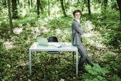 衣服的商人在他运转的办公桌附近在绿色公园 到达天空的企业概念金黄回归键所有权 图库摄影