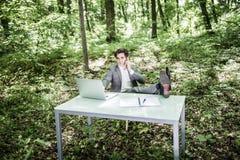 衣服的商人在有他的腿的绿色公园在手机的办公桌谈话 到达天空的企业概念金黄回归键所有权 图库摄影