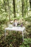 衣服的商人在有他的腿的绿色公园在手机的办公桌谈话 到达天空的企业概念金黄回归键所有权 库存图片