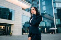 衣服的女实业家由室外的电话谈话 免版税图库摄影