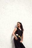 黑衣服的妇女与摆在白色backgr的金黄腰带 免版税图库摄影