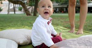 衣服的婴孩与看照相机的美丽的大眼睛坐自然 影视素材