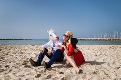 衣服的年轻人与红色礼服和帽子的妇女坐海滩 免版税图库摄影