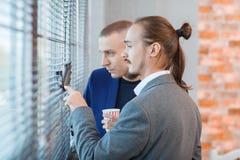 衣服的年轻人在一个大办公室窗口附近 库存照片