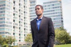 衣服的年轻英俊的非裔美国人的商人,看s 库存图片