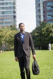 衣服的悦目年轻非裔美国人的商人, commu 库存照片