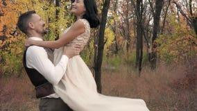 衣服的愉快的人在一名妇女的手一件长的礼服的,慢动作上旋转 股票视频