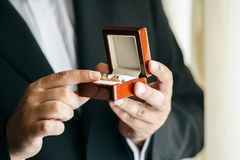 衣服的拿着婚戒的新郎和领带 免版税库存图片