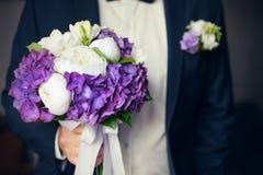 黑衣服的新郎与婚礼花束在他的手上 免版税库存照片