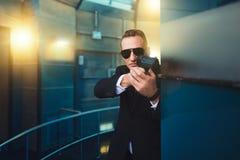 衣服的有枪的保镖和太阳镜在手上 库存照片